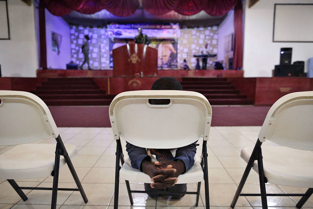 Jeccene Thimote, of Haiti, kneels in front of a folding chair in prayer during a service in Creole at The Ambassadors of Jesus Church in Tijuana, Mexico, on May 24.  (AP Photo/Gregory Bull)
