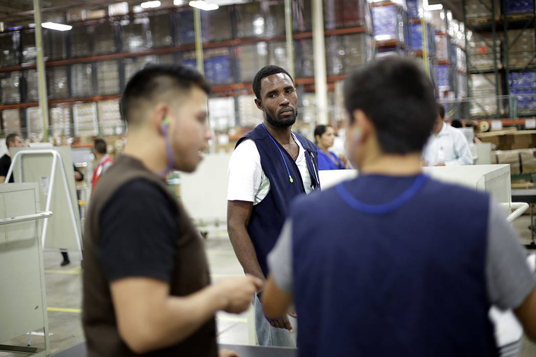 Rodin St. Surin, of Haiti, looks on as coworkers talk on the floor of a factory in Tijuana, Mexico, on June 6. (AP Photo/Gregory Bull)