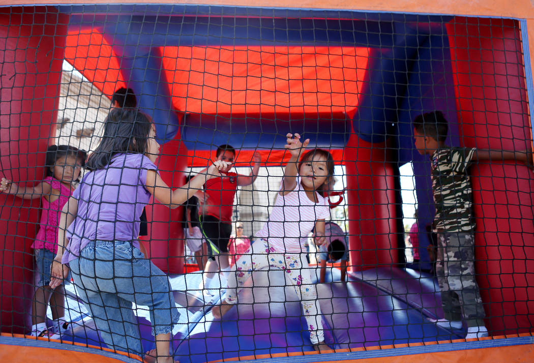 Kids play in a jump house during a Marianaճ Charity Foundation benefit for earthquake victims in Mexico supported by the Latin Chamber of Commerce at Mariana's Supermarket on West Sahara Ave ...
