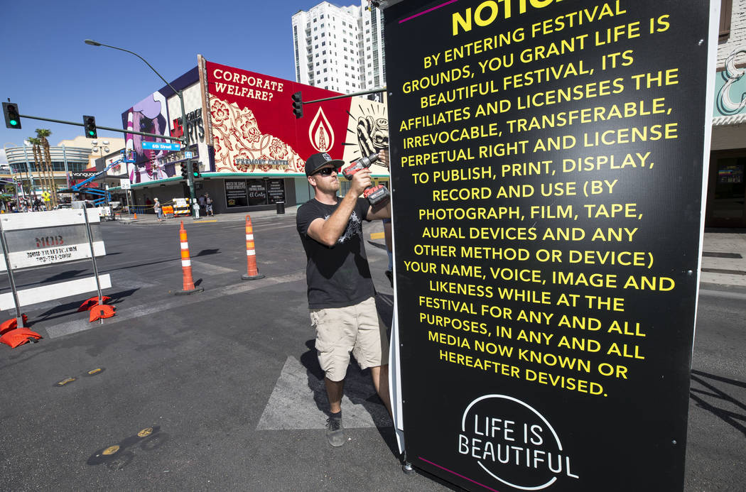 Sign installer Mark Fox, of Deluxe Designs, builds an informational sign near the intersection of 6th and East Fremont streets in preparation for the Life is Beautiful festival in downtown Las Veg ...