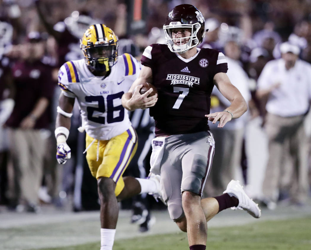Mississippi State quarterback Nick Fitzgerald (7) sprints past LSU safety John Battle (26) for a first down during the second half of their NCAA college football game in Starkville, Miss., Saturda ...