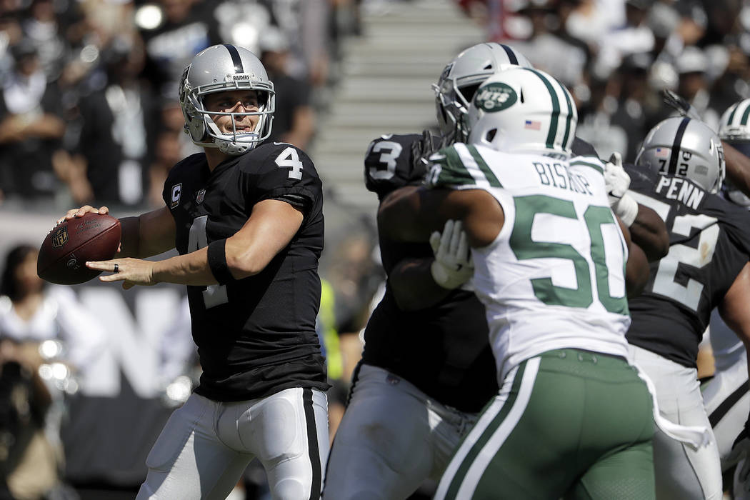 Oakland Raiders quarterback Derek Carr (4) passes as New York Jets linebacker Freddie Bishop (50) applies pressure during the first half of an NFL football game in Oakland, Calif., Sunday, Sept. 1 ...