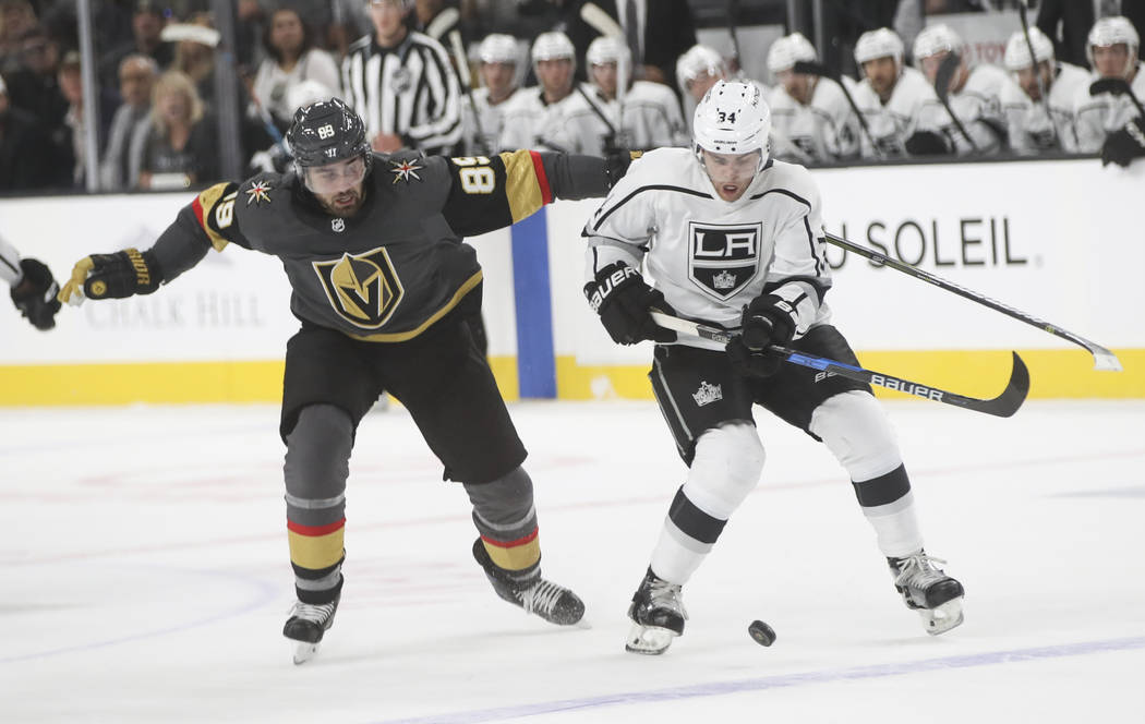 Los Angeles Kings' Kale Clague (34) gets control of the puck over Golden Knights' Alex Tuch (89) during an NHL preseason hockey game at T-Mobile Arena in Las Vegas on Tuesday, Sept. 26, 2017. Chas ...