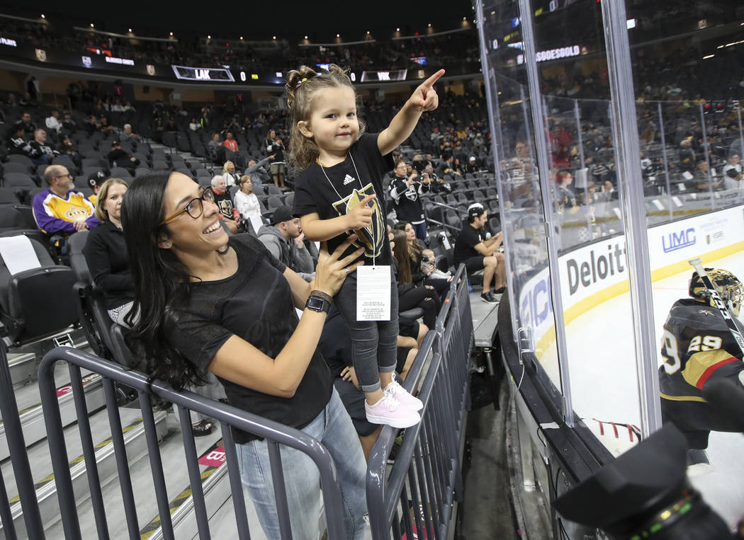 Two-year-old Olive Merrill, held by Jess Molina, points to her father, Golden Knights defenseman Jon Merrill, not pictured, as the team warms up before playing the Los Angeles Kings in an NHL pres ...