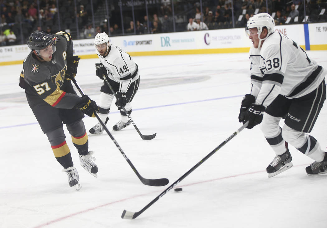 Golden Knights' David Perron (57) guides the puck as Los Angeles Kings' Paul LaDue (38) and Los Angeles Kings' Michael Mersch (49) defend during a preseason hockey game at T-Mobile Arena in Las Ve ...