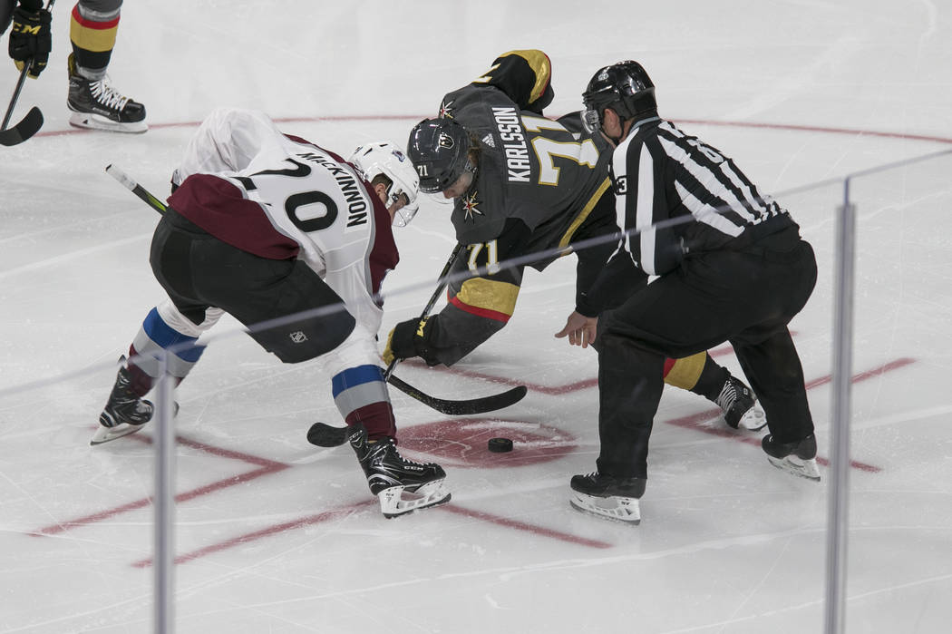 Colorado Avalanche center Rocco Grimaldi (20) and Vegas Golden Knights center William Karlsson (71) face off during the first period of a preseason NHL hockey game between the Vegas Golden Knights ...