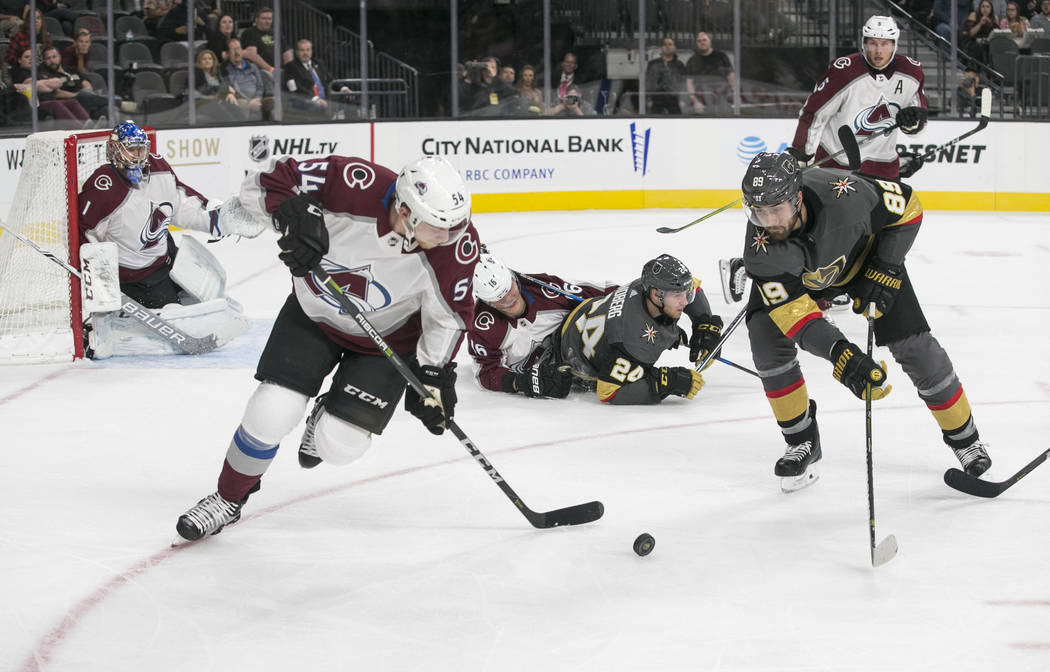 Colorado Avalanche defenseman Anton Lindholm (54) and Vegas Golden Knights right wing Alex Tuch (89) chase the puck during the second period of a preseason NHL hockey game between the Vegas Golden ...