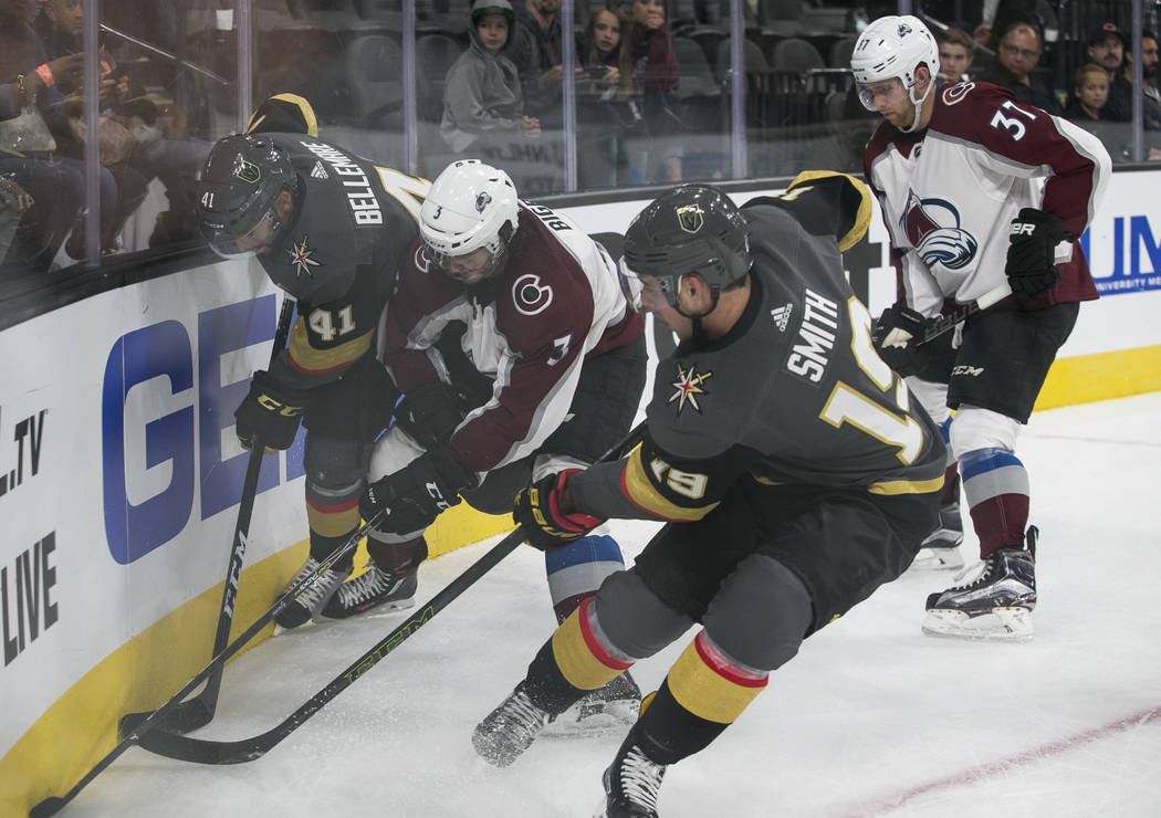 Colorado Avalanche defenseman Chris Bigras (3) is pressured by Vegas Golden Knights' Pierre-Edouard Bellemare (41) and Reilly Smith (19) during the second period of a preseason NHL hockey game bet ...