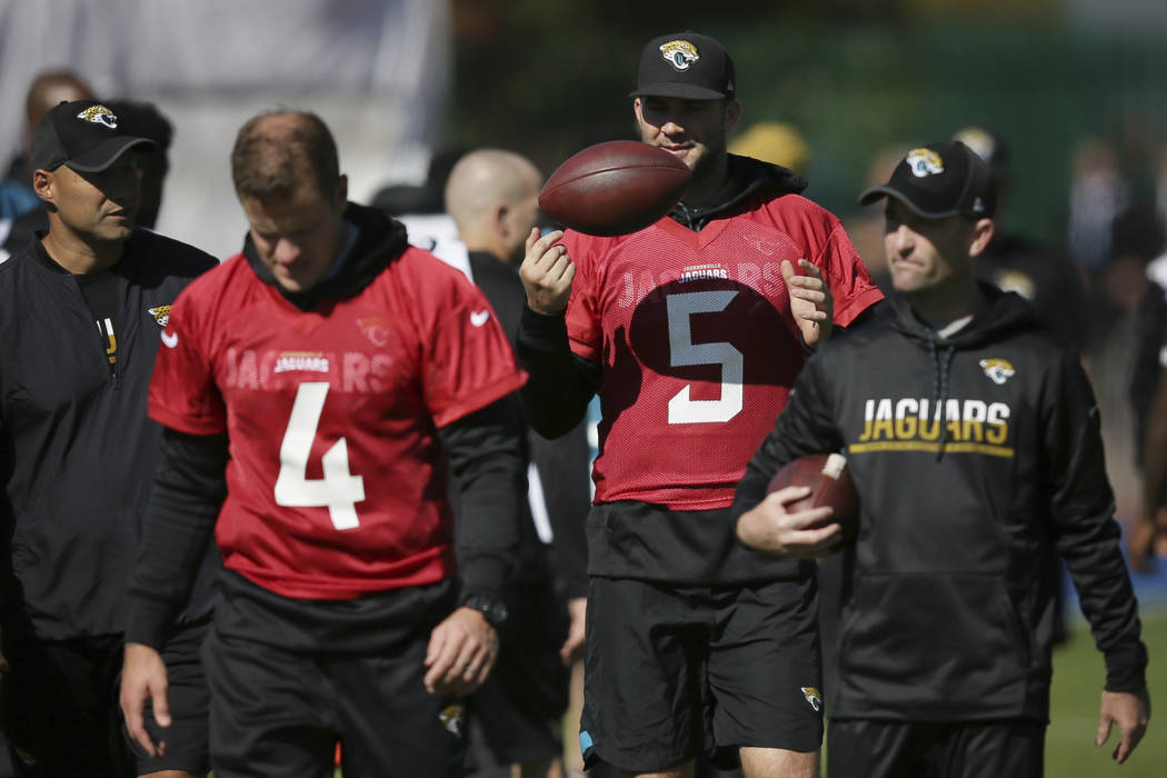 Jacksonville Jaguars quarterbacks Ryan Nassib, second left, and Blake Bortles, second right, walk across the pitch during a training session at Allianz Park in London, Friday Sept. 22, 2017. The J ...