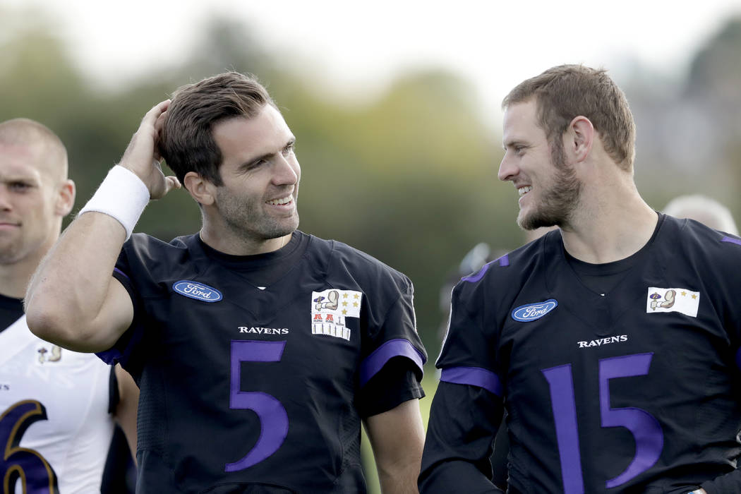 Baltimore Ravens first choice quarterback Joe Flacco, left, walks with quarterback Ryan Mallett as they leave the field at the end of a practice session at London Irish training ground in London,  ...