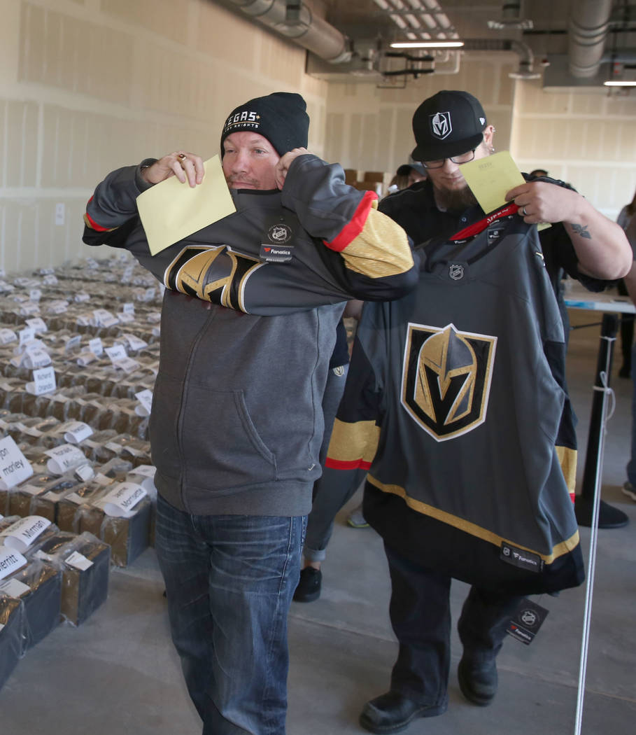 Kirk MacDonald, Golden Knights season ticket holder, tries on his new Golden Knights jersey at City National Center after receiving an exclusive membership kit and team's home jersey with commemor ...