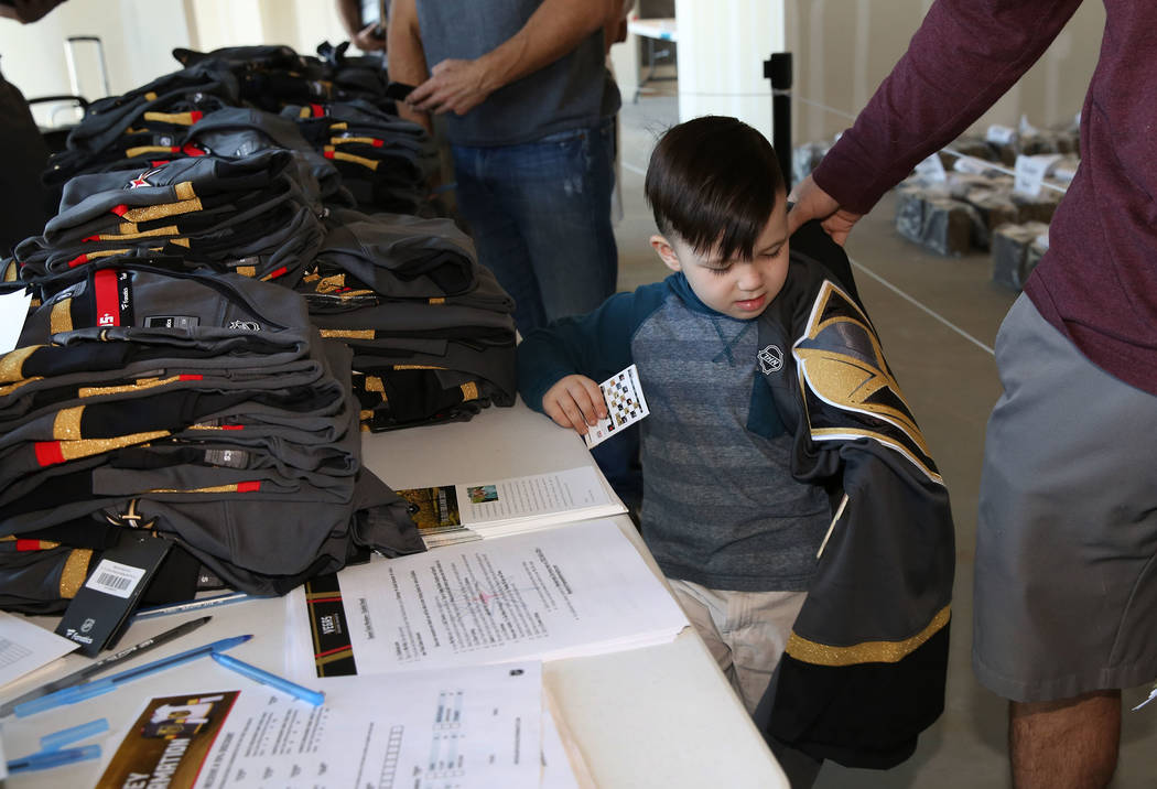 Kevin Fourman, right, Golden Knights season ticket holder, places his new Golden Knights jersey on his son Kellen, 4, inside City National Center after receiving an exclusive membership kit and te ...