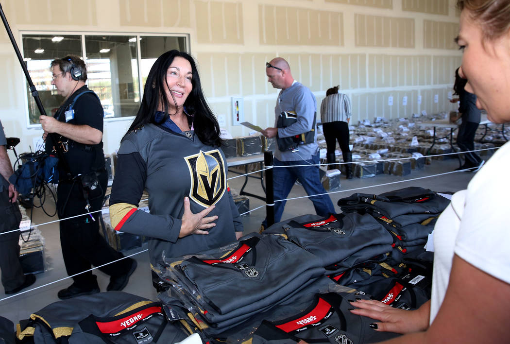 Stephanie Hodges shows off her new Golden Knights jersey inside City National Center after receiving an exclusive team's home jersey during season ticket members jersey pick up event on Friday, Se ...