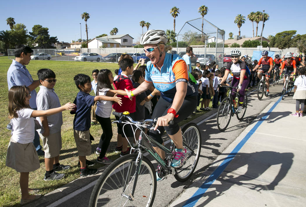Safe Routes to School Coordinator Traci Traasdahl is greeted by students as she arrives at Dailey Elementary School for a book giveaway on Friday, Sept. 22, 2017, in Las Vegas. Better World Books  ...