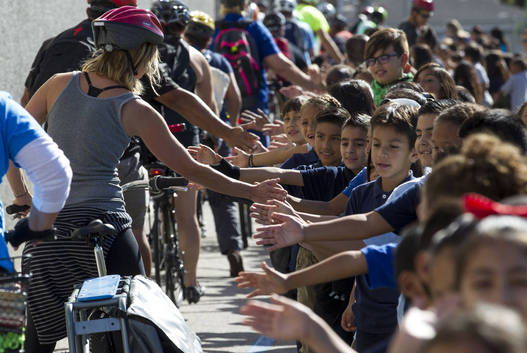 Dailey Elementary School students, right, welcome a group of cyclists arriving at the school for a book giveaway on Friday, Sept. 22, 2017, in Las Vegas. Better World Books donated 1,200 books tha ...