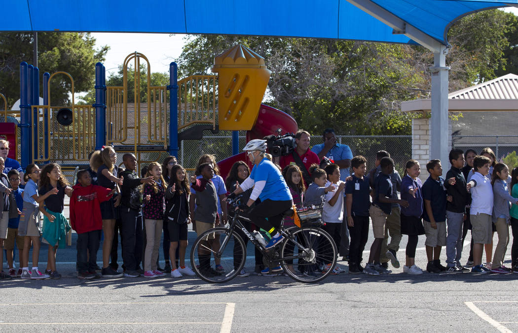Dailey Elementary School students welcome a group of cyclist arriving at their school for a book giveaway on Friday, Sept. 22, 2017, in Las Vegas. Better World Books donated 1,200 books that were  ...