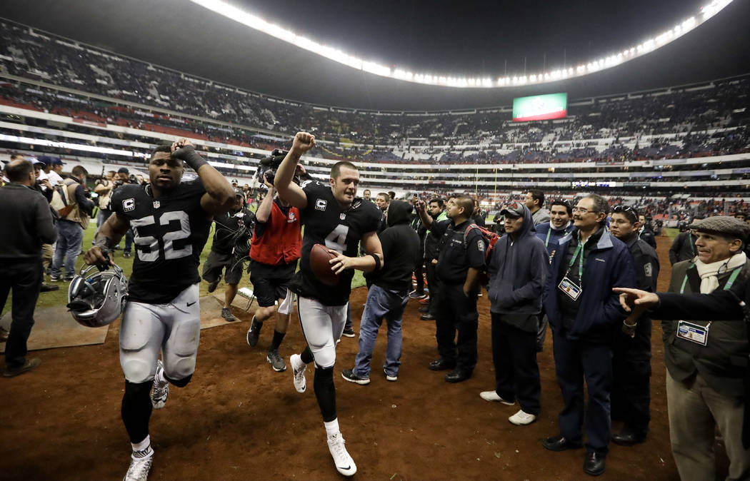 Oakland Raiders quarterback Derek Carr, center, and defensive end Khalil Mack (52) celebrate after their NFL football game against the Houston Texans Monday, Nov. 21, 2016, in Mexico City. The Rai ...