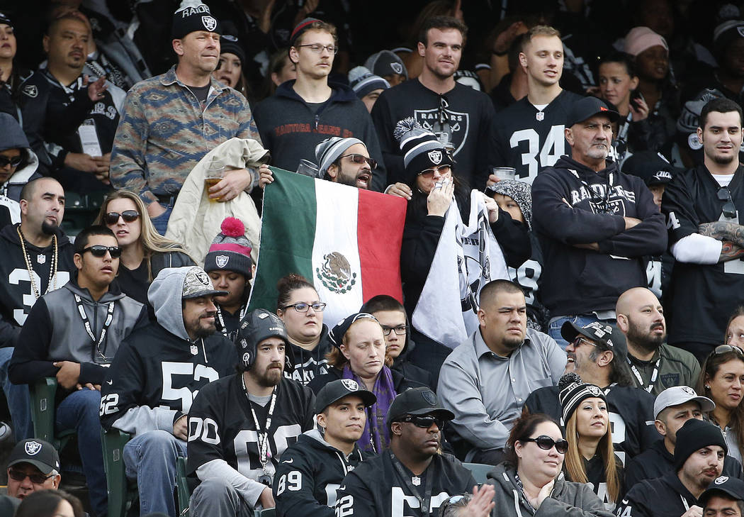 A man holds up a flag of Mexico during the second half of an NFL football game between the Oakland Raiders and the Carolina Panthers in Oakland, Calif., Sunday, Nov. 27, 2016. (AP Photo/Tony Avelar)