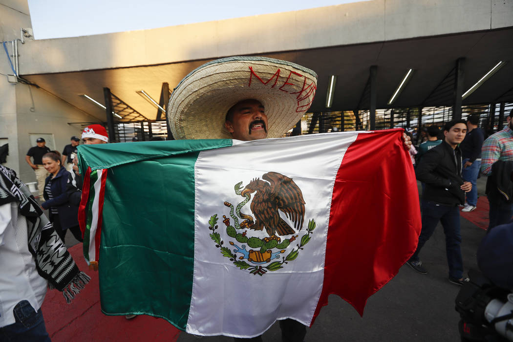 An Oakland Raiders fan carries a Mexican flag as he arrives to Azteca Stadium before an NFL football game against the Houston Texans Monday, Nov. 21, 2016, in Mexico City. (AP Photo/Eduardo Verdugo)