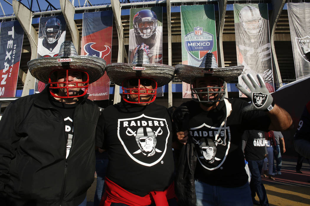 In this Monday, Nov. 21, 2016 photo, Oakland Raiders fans pose for a picture in front of Azteca Stadium before an NFL football game against the Houston Texans in Mexico City. The game drew a large ...
