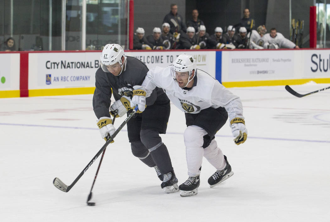 Vegas Golden Knights forward Nick Suzuki, left, (17) and Golden Knights left defenseman Brad Hunt (77) vie for the puck in a scrimmage game during the NHL team's practice at the City National Aren ...