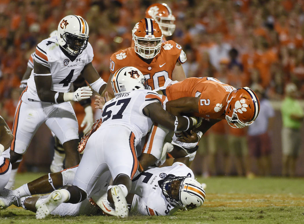 Clemson quarterback Kelly Bryant (2) is tackled by Auburn defensive lineman Derrick Brown (5) and Auburn linebacker Deshaun Davis (57) during the second half of an NCAA college football game, Satu ...