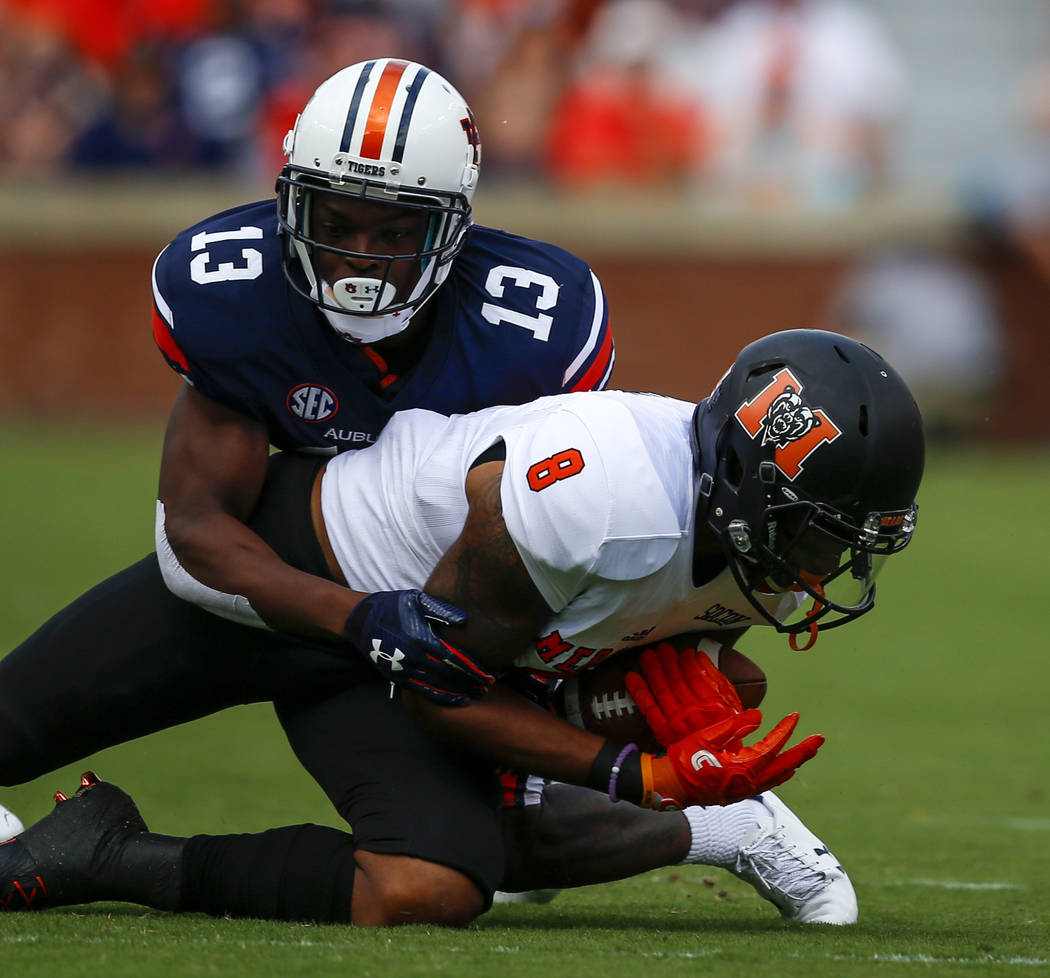 Mercer wide receiver Marquise Irvin (8) catches a pass as Auburn defensive back Javaris Davis (13) tackles him during the first half of an NCAA college football game, Saturday, Sept. 16, 2017, in  ...