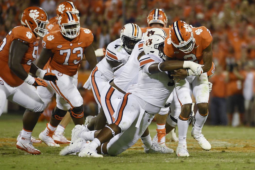Clemson quarterback Kelly Bryant (2) is tackled by Auburn defensive lineman Derrick Brown (5) during the second half of an NCAA college football game, Saturday, Sept. 9, 2017, in Clemson, S.C. Cle ...