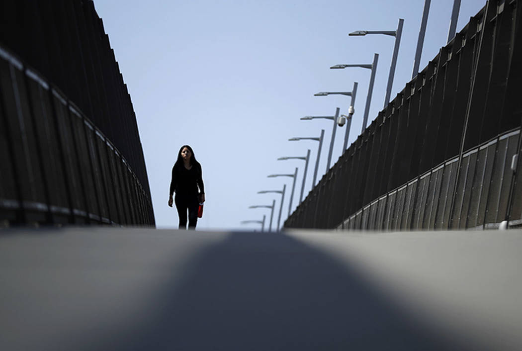 In this Tuesday, Sept. 19, 2017, photo, a woman walks towards the border on a pedestrian bridge over construction on a new curve along California's Interstate 5 as it approaches the border with Ti ...