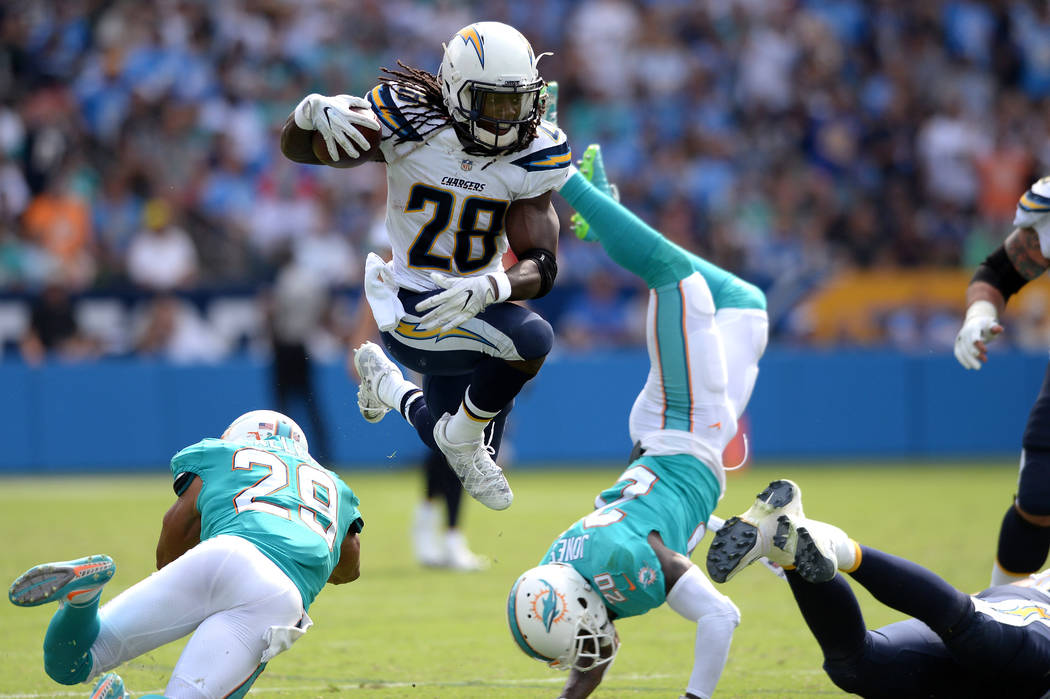 Los Angeles Chargers running back Melvin Gordon jumps to elude the tackle of Miami Dolphins defensive back Nate Allen (29) and free safety Reshad Jones (20) during the second half on Sunday, Sept. ...