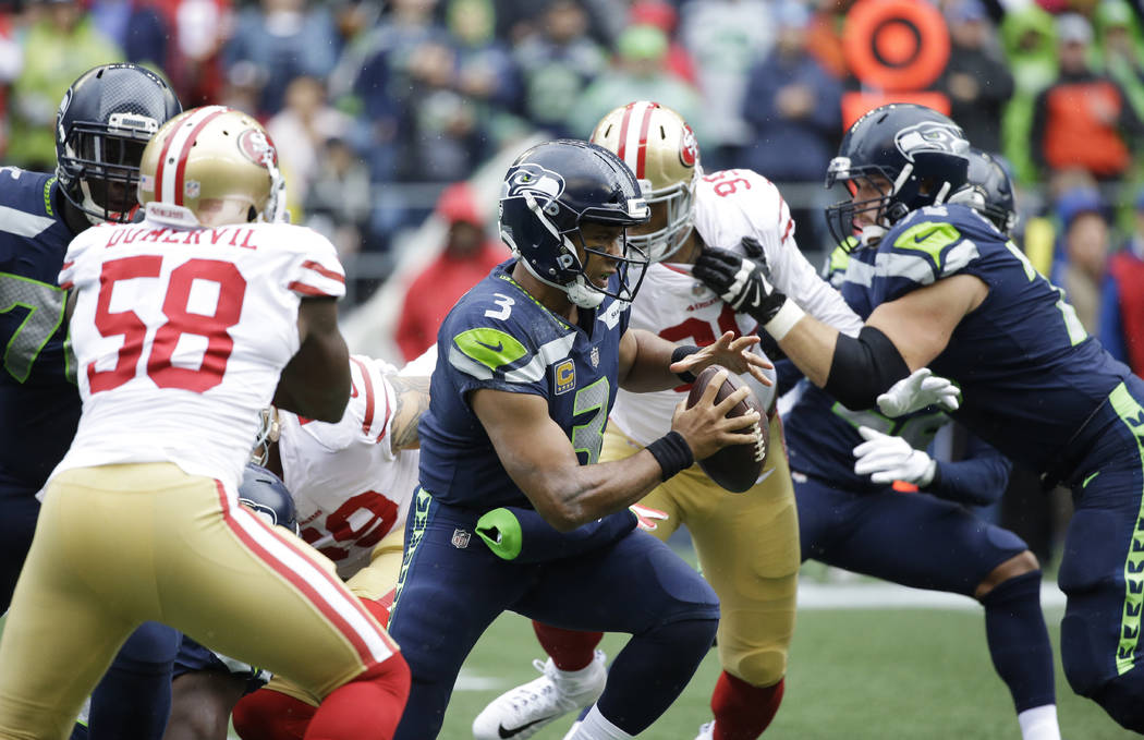 Seattle Seahawks quarterback Russell Wilson, center, scrambles against the San Francisco 49ers in the first half of an NFL football game, Sunday, Sept. 17, 2017, in Seattle. (AP Photo/Elaine Thompson)