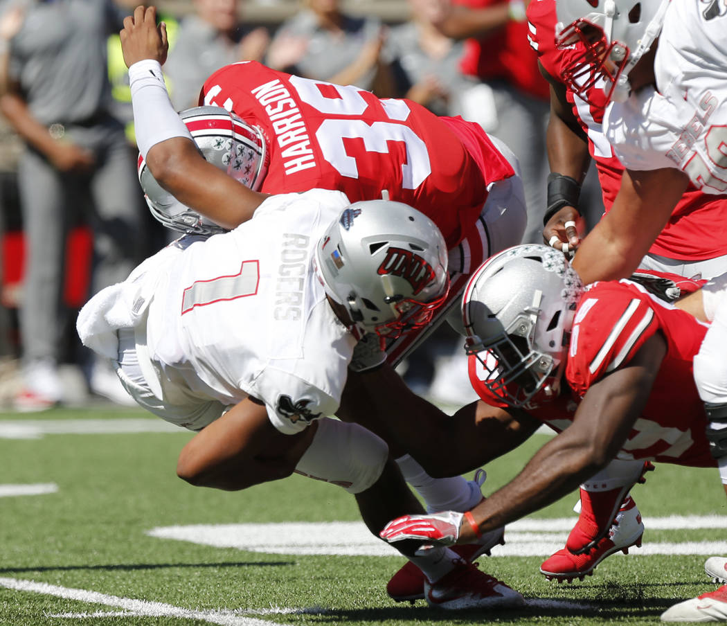 Ohio State linebacker Malik Harrison, top, and defensive lineman Tyquan Lewis, right, sack UNLV quarterback Armani Rogers during the first half of an NCAA college football game Saturday, Sept. 23, ...