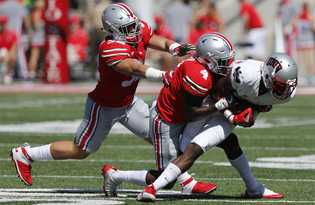 Ohio State defenders Tuf Borland, left, and Jordan Fuller, center, tackle UNLV wide receiver Kendal Keys during the first half of an NCAA college football game Saturday, Sept. 23, 2017, in Columbu ...