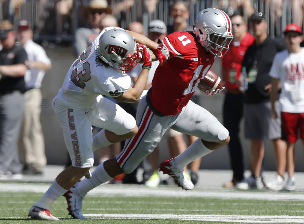 Ohio State receiver Austin Mack, right, stiff arms UNLV defensive back Dalton Baker during the first half of an NCAA college football game Saturday, Sept. 23, 2017, in Columbus, Ohio. (AP Photo/Ja ...