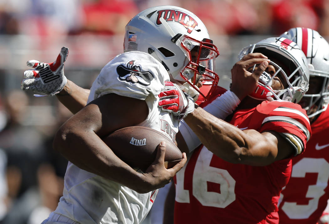 UNLV quarterback Armani Rogers, left, stiff arms Ohio State linebacker Keandre Jones during the second half of an NCAA college football game Saturday, Sept. 23, 2017, in Columbus, Ohio. Ohio State ...