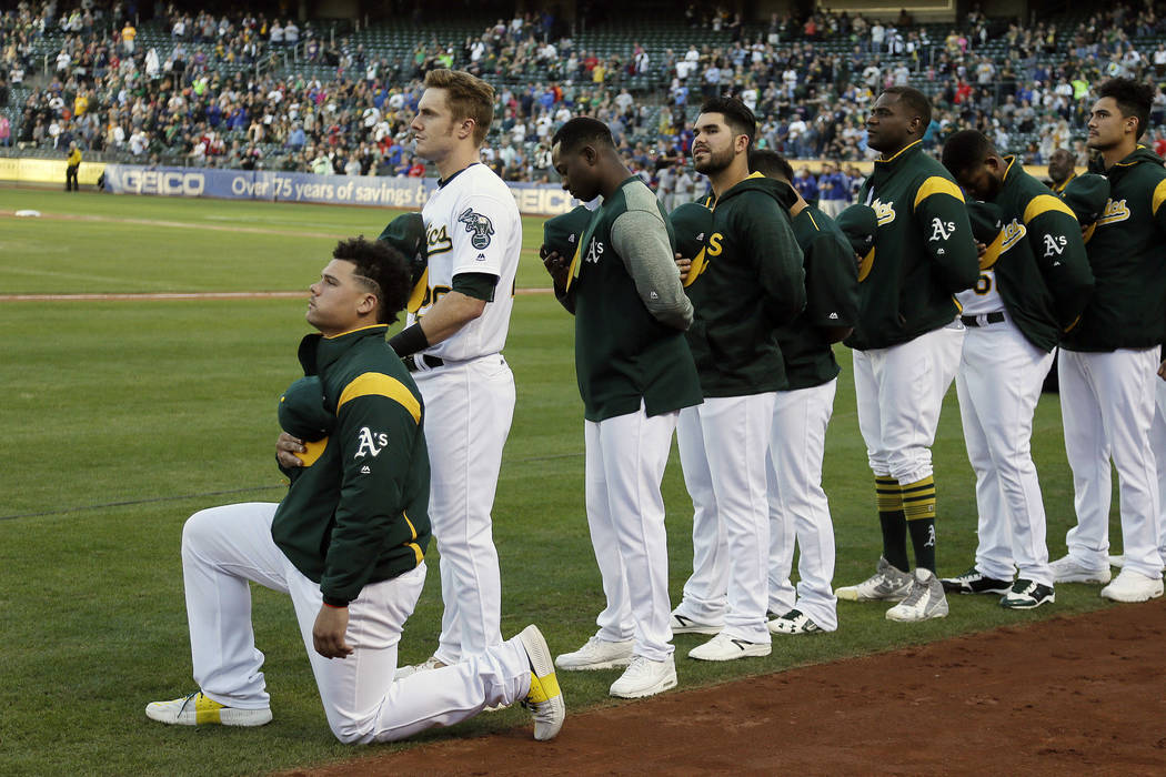 Oakland Athletics catcher Bruce Maxwell kneels during the National Anthem before the start of a baseball game against the Texas Rangers Saturday, Sept. 23, 2017, in Oakland, Calif. Bruce Maxwell o ...