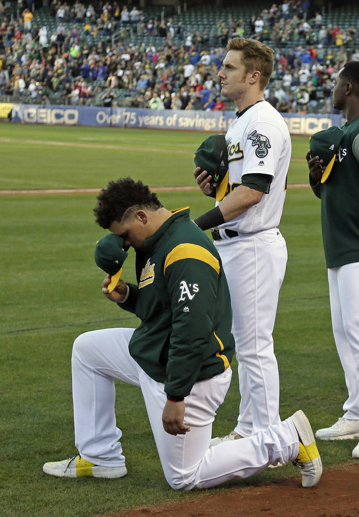 Oakland Athletics catcher Bruce Maxwell, left, kneels as teammate Mark Canha, right, looks on during the National Anthem before the start of a baseball game against the Texas Rangers Saturday, Sep ...