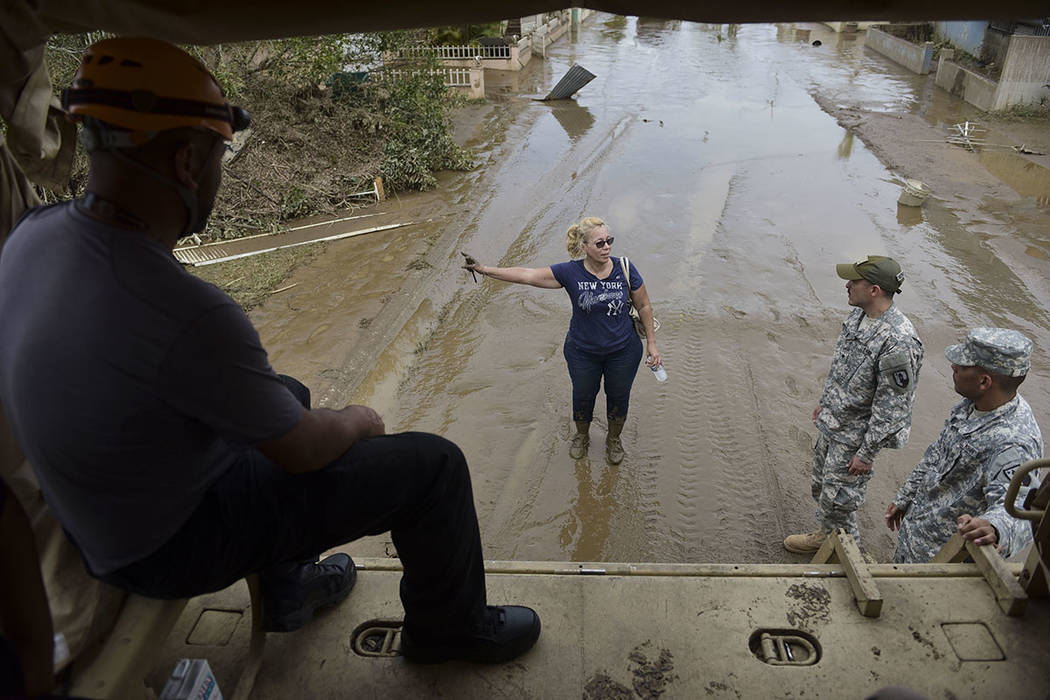 National Guard personnel offer evacuation to a Toa Ville resident after the passing of Hurricane Maria, in Puerto Rico, Friday, September 22, 2017. (AP Photo/Carlos Giusti)