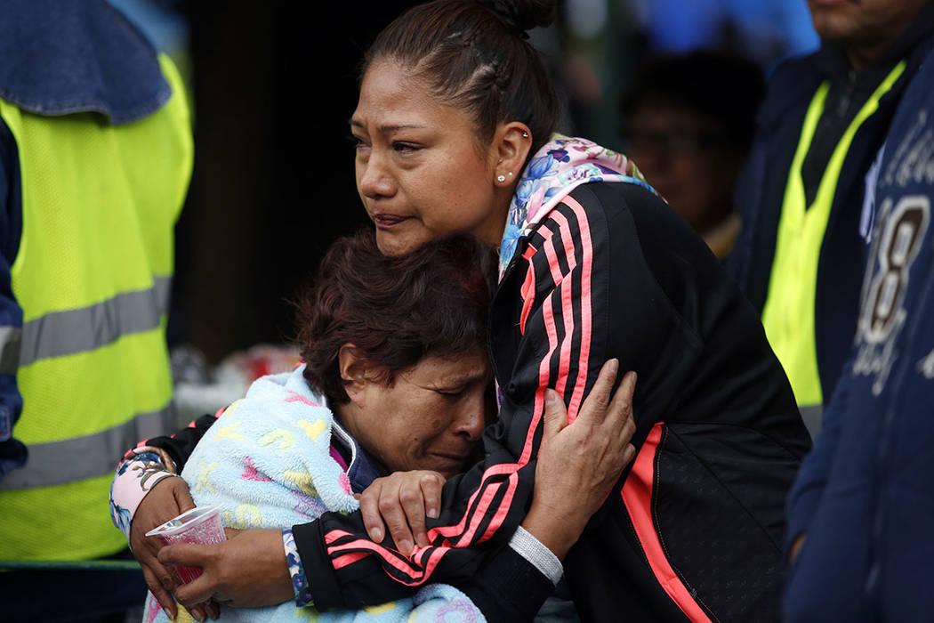 Family members embrace as they wait for news of their relatives outside a quake-collapsed seven-story building in Mexico City's Roma Norte neighborhood, Friday, Sept. 22, 2017.  (AP Photo/Rebecca  ...