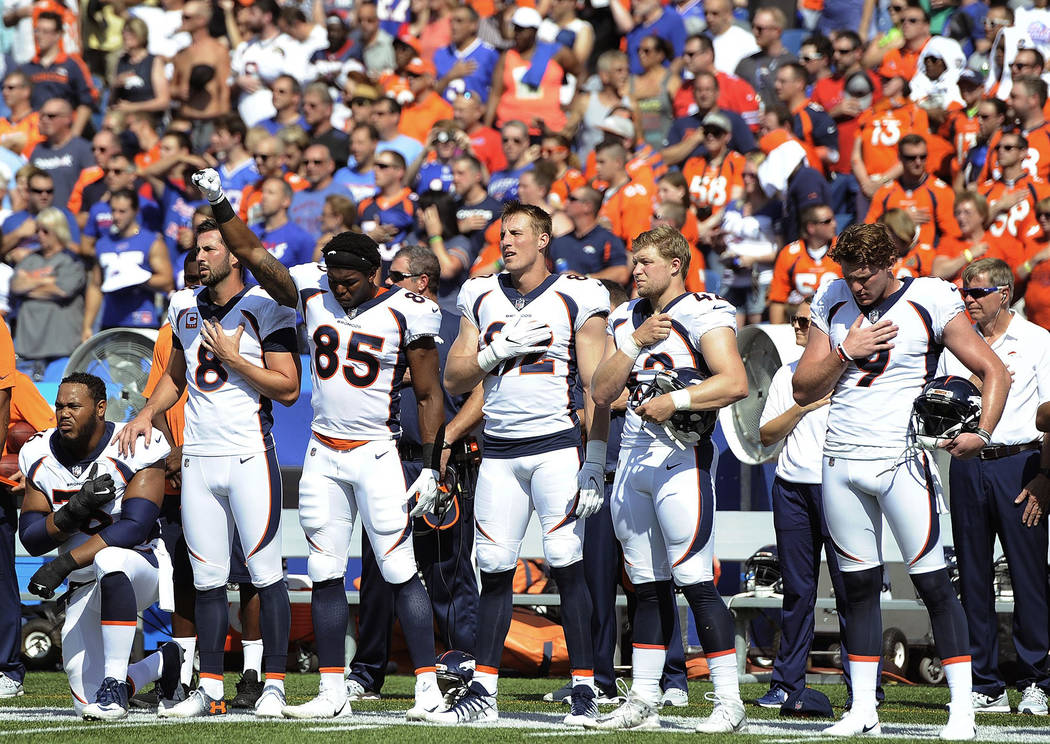 Denver Broncos tight end Virgil Green (85) gestures as teammate Max Garcia, left, takes a knee during the playing of the national anthem prior to an NFL football game against the Buffalo Bills, Su ...