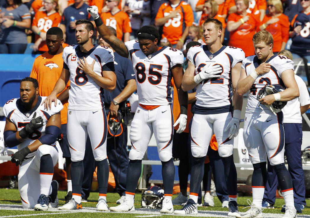 Denver Broncos tight end Virgil Green (85) gestures and offensive guard Max Garcia, left, kneels during the playing of the national anthem prior to an NFL football game against the Buffalo Bills,  ...