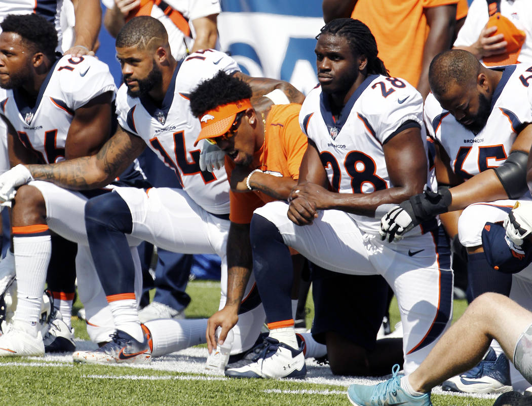 Denver Broncos players, including Jamaal Charles (28) kneel during the national anthem prior to an NFL football game against the Buffalo Bills, Sunday, Sept. 24, 2017, in Orchard Park, N.Y. (AP Ph ...