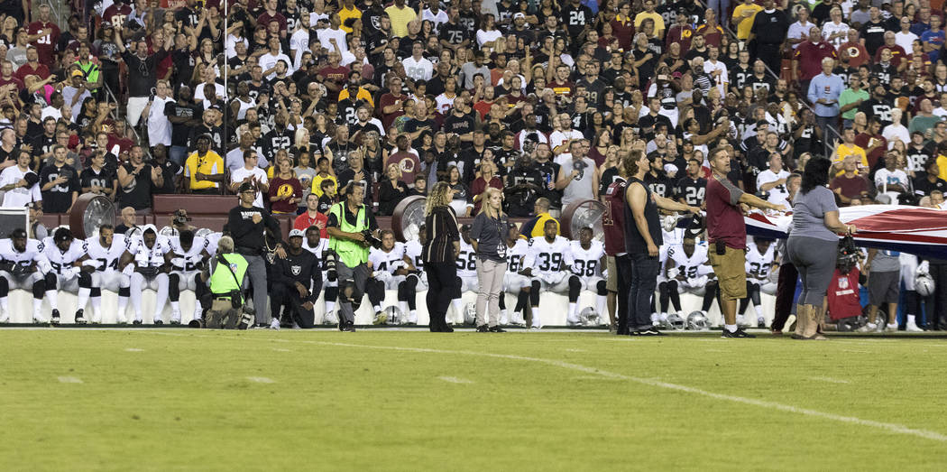 The Oakland Raiders interlock arms and sit during the national anthem before their game against the Washington Redskins in Landover, Md., Sunday, Sept. 24, 2017. Heidi Fang Las Vegas Review-Journa ...
