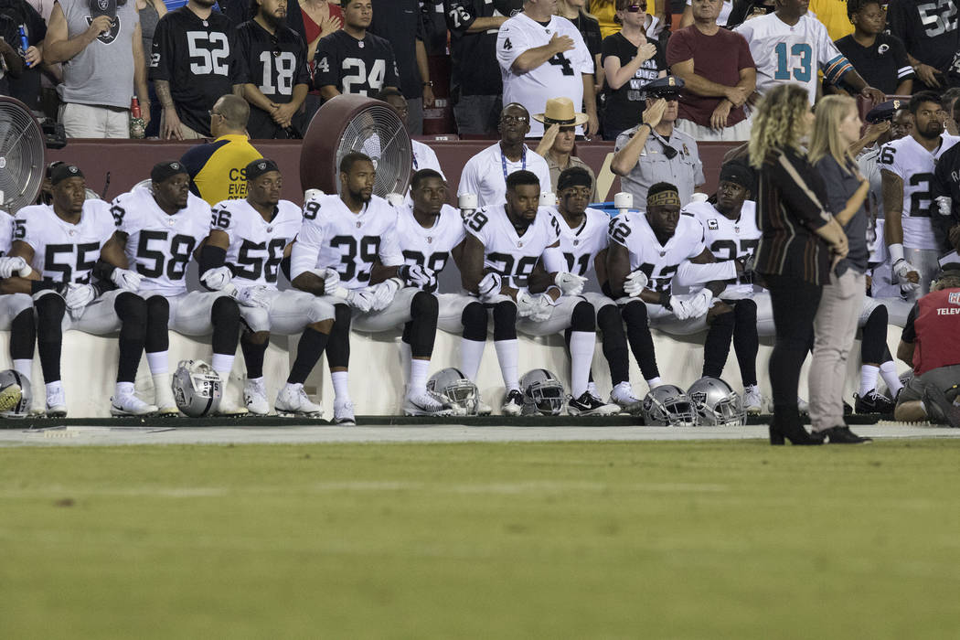 Some of the Oakland Raiders interlock arms and sit during the national anthem before their game against the Washington Redskins in Landover, Md., Sunday, Sept. 24, 2017. Heidi Fang Las Vegas Revie ...