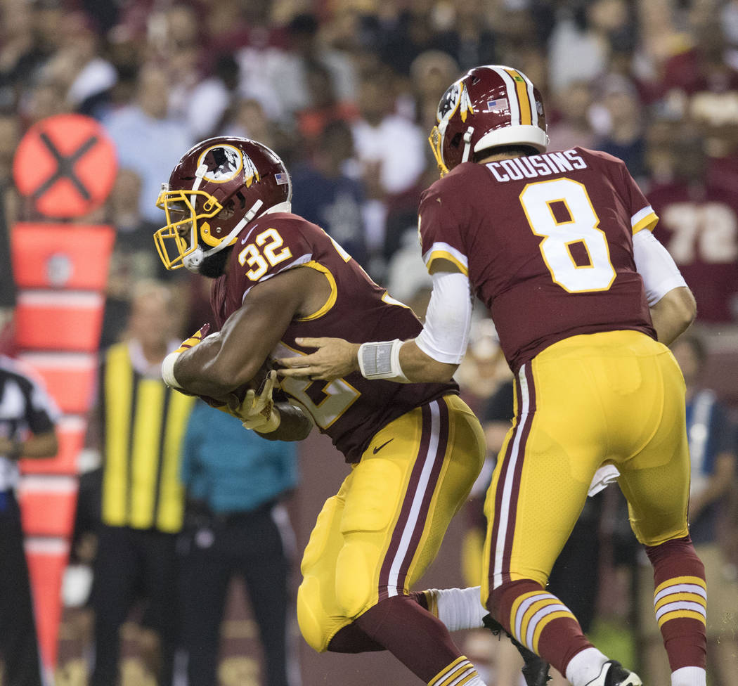 Washington Redskins quarterback Kirk Cousins (8) hands off the football to Washington Redskins running back Samaje Perine (32) in the first half of their game against the Oakland Raiders in Landov ...