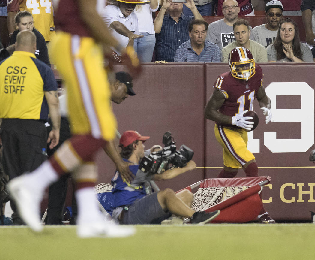 Washington Redskins wide receiver Terrelle Pryor (11) runs into a cameraman on the sideline after making a catch in the first half of their game against the Oakland Raiders in Landover, Md., Sunda ...
