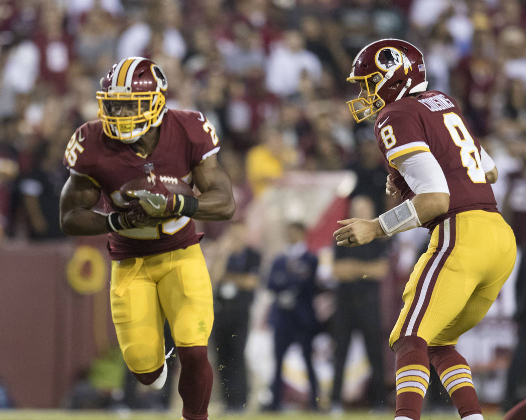 Washington Redskins quarterback Kirk Cousins (8) hands off the football to running back Chris Thompson (25) in the second half of their game in Landover, Md., Sunday, Sept. 24, 2017. Heidi Fang La ...