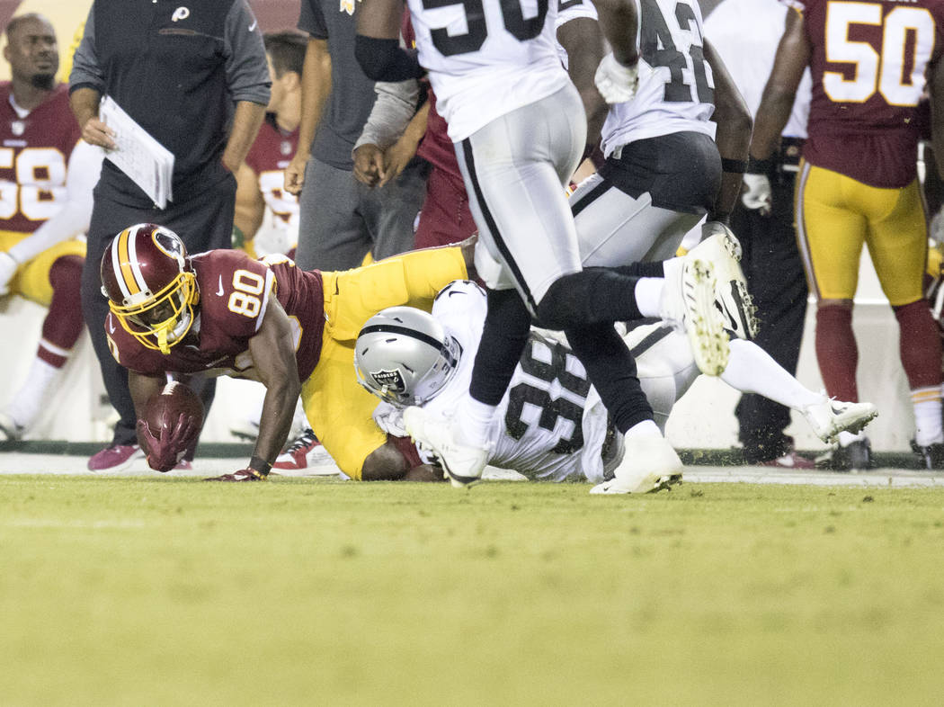 Washington Redskins wide receiver Jamison Crowder (80) is tackled by Oakland Raiders cornerback T.J. Carrie (38) after a catch in the second half of their game at the FedEx Field in Landover, Md., ...