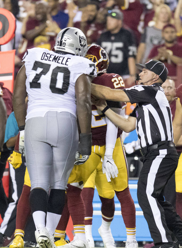 Oakland Raiders offensive guard Kelechi Osemele (70) argues with Washington Redskins strong safety Deshazor Everett (22) in the first half of their game in Landover, Md., Sunday, Sept. 24, 2017. H ...