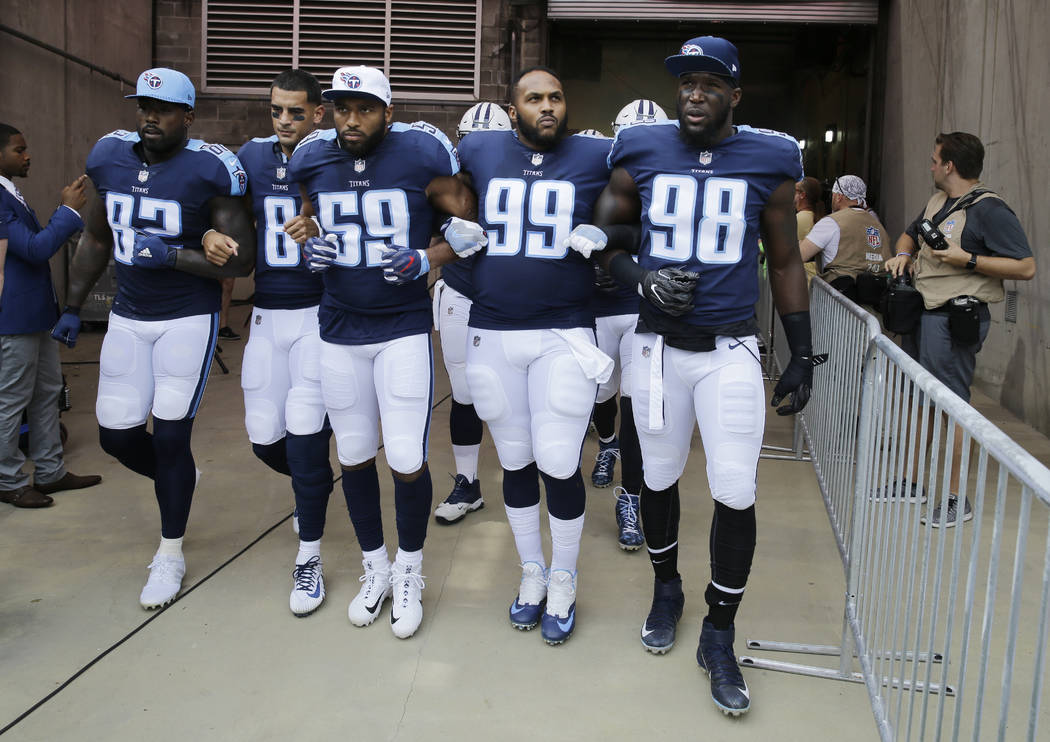 Tennessee Titans players walk to the field with arms linked after the national anthem had been played before an NFL football game between the Titans and the Seattle Seahawks Sunday, Sept. 24, 2017 ...